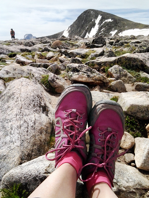 Merrell Proterra Vim Sports taking a break atop Flattop Mountain, with Hallett Peak in the background.